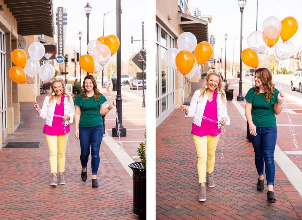 two women walking down a city street with balloons